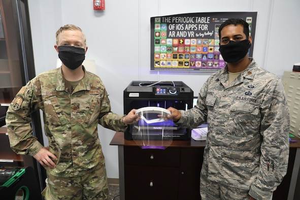 Two Airmen stand together holding a face mask they made using a 3-D printer.