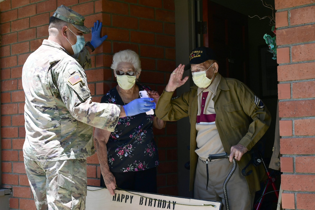 A solider holds a phone while showing a retired soldier his family.
