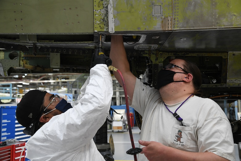 Juan Gutierrez, left, and Jeff Schmitt, 309th Aircraft Maintenance Group sheet metal mechanics, work on an F-16 at Hill Air Force Base, Utah, May, 8, 2020. Comprised of seven maintenance squadrons and more than 2,000 personnel, the 309th AMXG performs depot maintenance, repair and overhaul on A-10, C-130, F-16, F-22, F-35 and T-38 airframes. (U.S. Air Force photo by R. Nial Bradshaw)