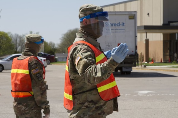 Spc. Colton Fenton and Spc. Kellen Korf with Headquarters and Headquarters Company, 248th Aviation Support Battalion, Iowa Army National Guard, operate a traffic control checkpoint at a pop-up COVID-19 testing site at West Middle School in Muscatine, Iowa, April 30, 2020. Almost 46,000 National Guard troops are assisting their states in response to the COVID-19 pandemic, and many are now eligible for financial assistance from Army Emergency Relief.