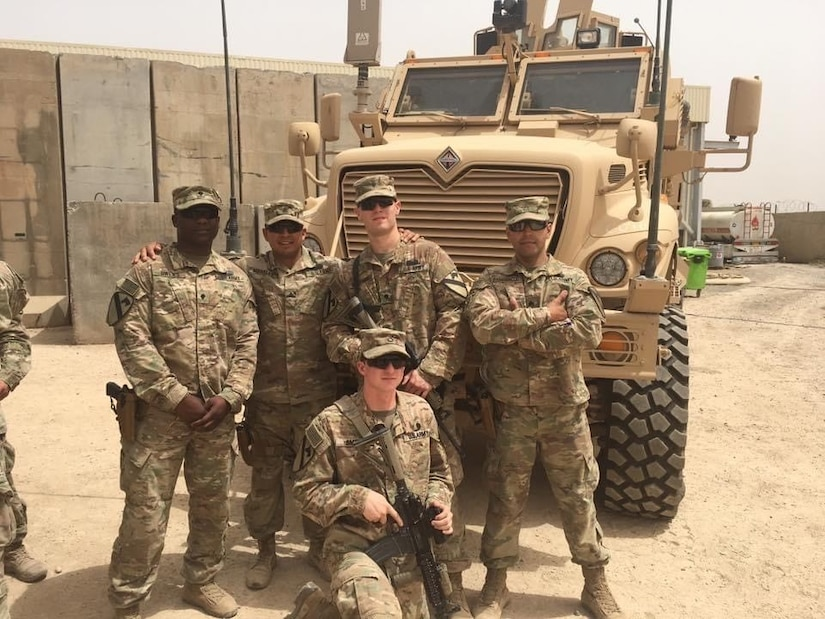 six men in green camouflage uniforms and caps with 9mm pistols in holsters on sides and one holds an M4 rifle stand in front of a military vehicle.