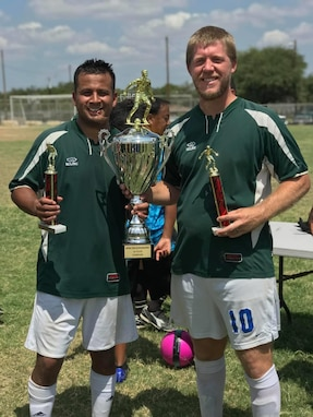 Hispanic male and white male in green jerseys and white shorts hold one large trophy and two little trophies.