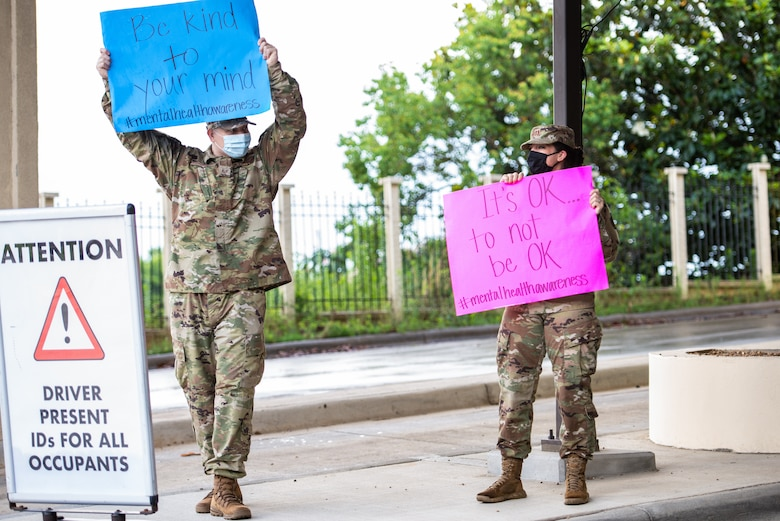 two Airman hold signs up outside the Day Street gate.