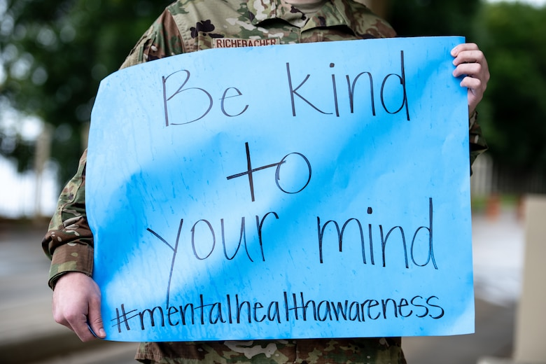 Airman holds up sign that reads, be kind to your mind.