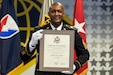 Command Sgt. Maj. Courtney M. Ross, U.S. Army Financial Management Command senior enlisted advisor, grins as he shows off his certificate of retirement during a ceremony at the Maj. Gen. Emmett J. Bean Federal Center in Indianapolis May 15, 2020. Ross, a native of North Augusta, South Carolina, joined the Army as an accounting specialist in 1996.