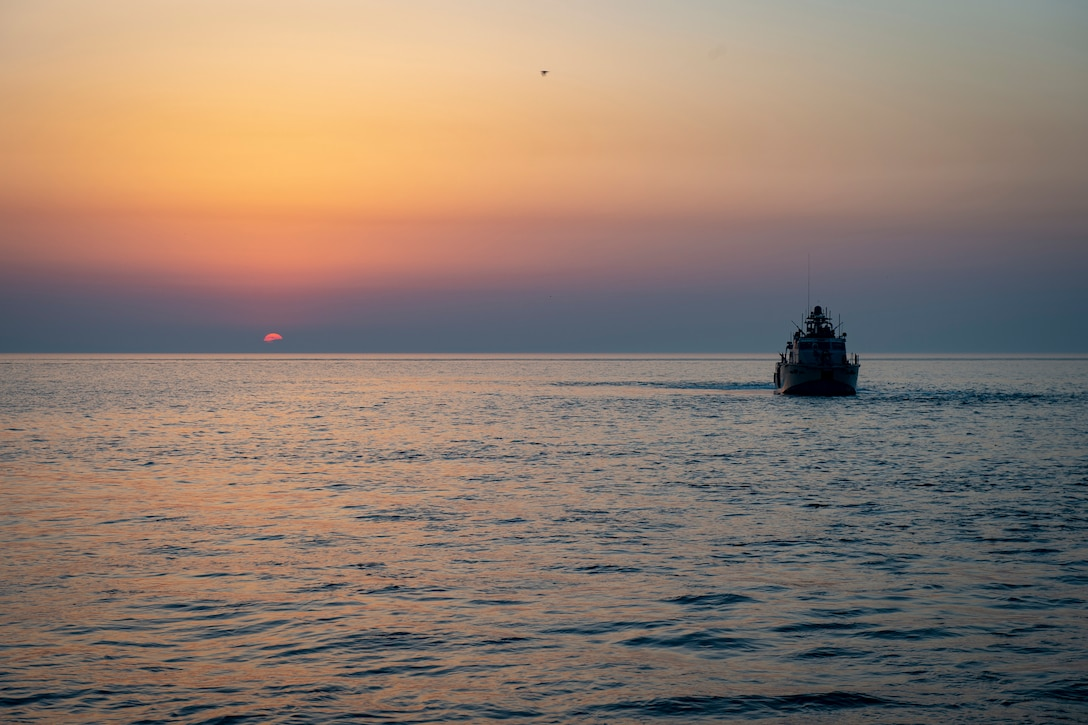 A military patrol boat moves along the water at twilight.