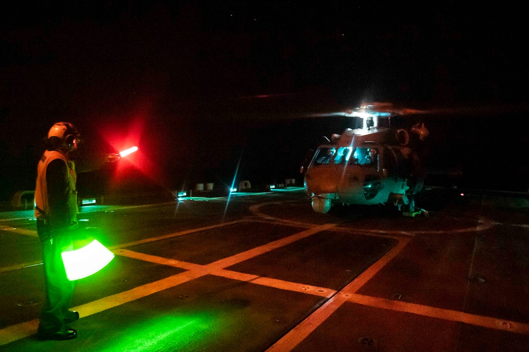 A military helicopter prepares to take off from a ship at night.