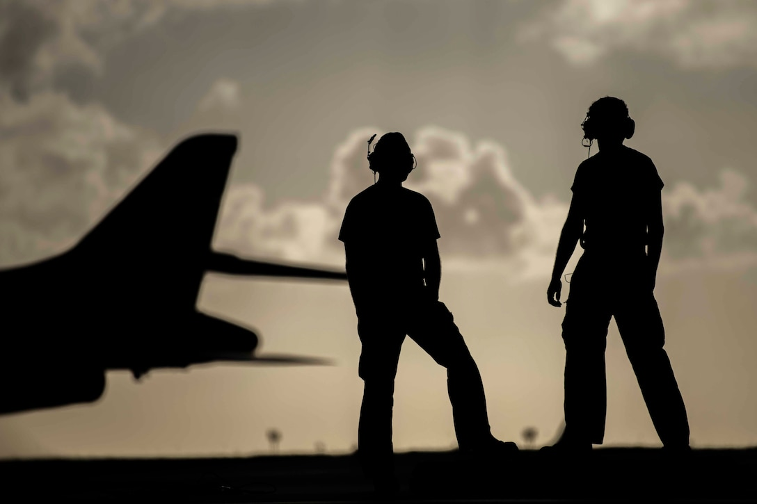 Two airmen, shown in silhouette, stand next to each other with an aircraft in the background.