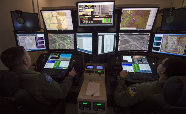 two Airmen sit in front of multiple monitors in dark room