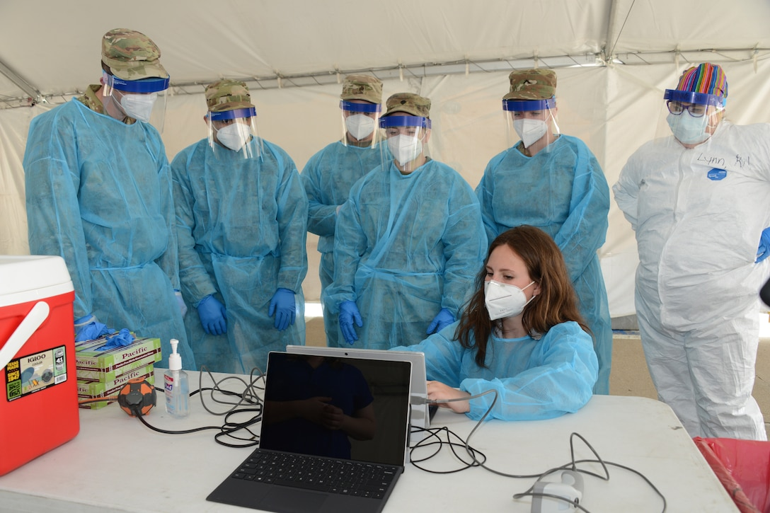 A group of National Guardsmen in medical uniforms stand behind a woman on a computer.