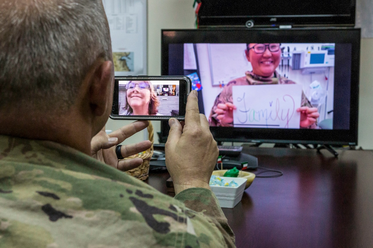 "A soldier holds up a phone that has his wife on screen, while looking at a person on another screen who holds a sign that says ""Family"""