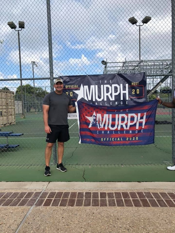 U.S. Air Force Col. Robert Ramirez, 17th Training Wing vice commander, holds The Murph Challenge flag after completing The Murph Challenge at the Mathis Fitness Center on Goodfellow Air Force Base, Texas, May 25, 2020. 17th Training wing leadership paid their respects to U.S. Navy Lt. Michael P. Murphy by partaking in the challenge. (Courtesy photo)