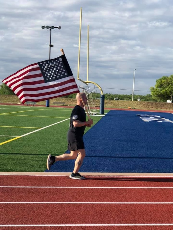 U.S. Air Force Col. Andres Nazario, 17th Training Wing commander, runs on the track behind the Mathis Fitness Center during The Murph Challenge, on Goodfellow Air Force Base, Texas, May 25, 2020. The challenge consisted of a one-mile run followed by 100 pull-ups, 200 push-ups, 300 air squats, and finished with a one-mile run, all while wearing a 20-pound vest. (Courtesy photo)