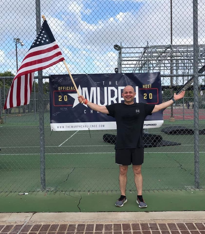 U.S. Air Force Col. Andres Nazario, 17th Training Wing commander, holds an American flag after completing the Murph Challenge on the pad near the Mathis Fitness Center, May 25, 2020.  Goodfellow had nearly 100 social-distancing participants on site and virtually. (Courtesy photo)