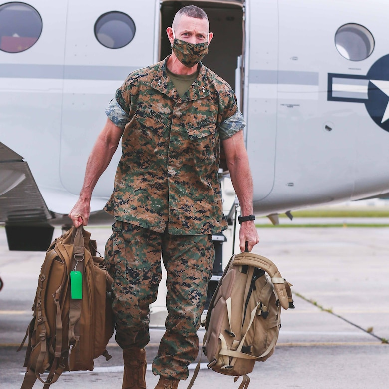 Marine Corps general wearing a face mask walks off a military aircraft.