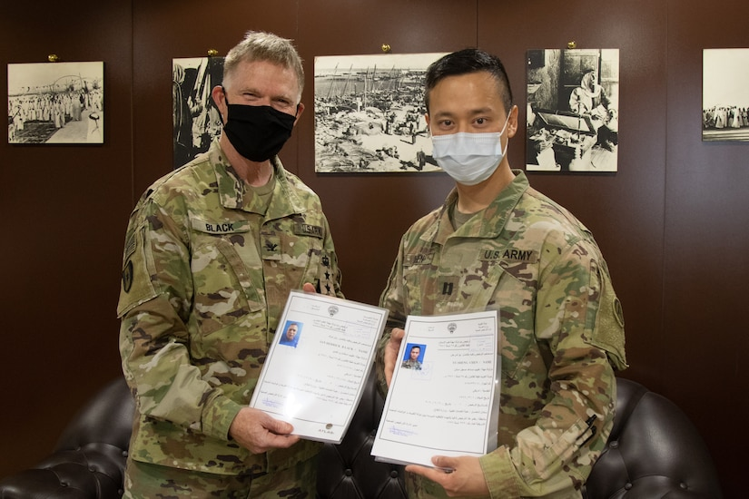 U.S. Army Col. Ian Black, command surgeon for the 1st Theater Sustainment Command, left, and U.S. Army Capt. Yusheng Chen, command dentist for Area Support Group - Kuwait, present their Kuwaiti medical-licenses at the Kuwait Armed Forces Hospital in Sabah Al Salem, Kuwait, May 19, 2020. Black and Chen are the first U.S. military personnel to be medically licensed for practice in Kuwait, an initial step towards medical interoperability between the two nations. (U.S. Army photo by Sgt. Sean Harding)