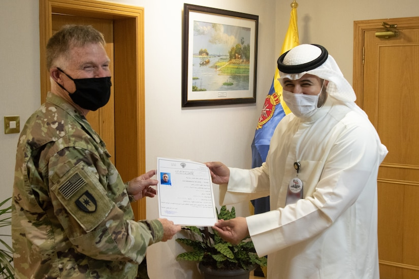 U.S. Army Col. Ian Black, command surgeon for the 1st Theater Sustainment Command, receives his Kuwaiti medical license from Sheik Abdullah M. Al-Sabah, chief of medical services for the Kuwait Ministry of Defense, at the Kuwait Armed Forces Hospital in Sabah Al Salem, Kuwait, May 19, 2020. Black is one of the first two U.S. military personnel now licensed to practice medicine at Kuwait Ministry of Defense hospitals, an initial step toward achieving medical interoperability between the two nations. (U.S. Army photo by Sgt. Sean Harding)