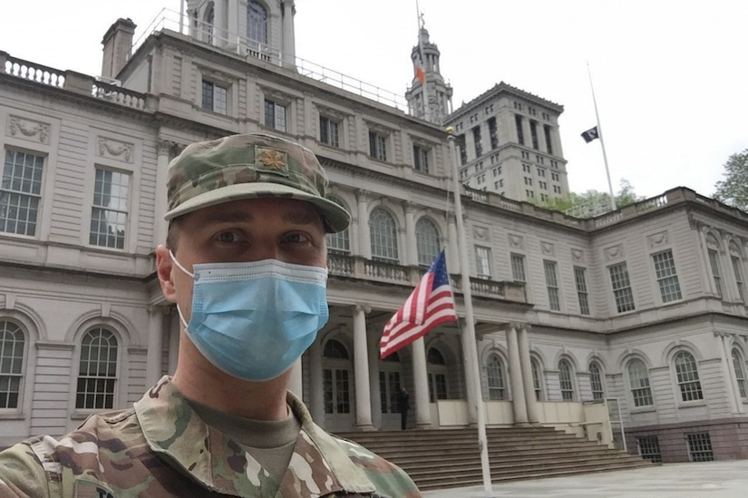 A man dressed in a military uniform and wearing a face mask poses for a photo in front of a large building where the flag is flying at half-staff.