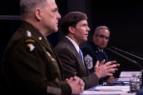 Three defense leaders sit behind a long table at a briefing.