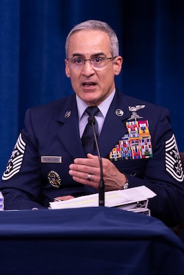 A man in uniform speaks into a microphone.
