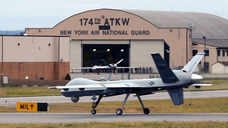 MQ-9 Reaper sits on runway in front of hangar