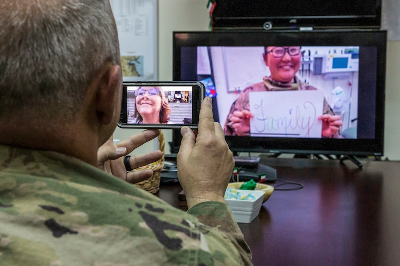 """A soldier holds up a phone that has his wife on screen, while looking at a person on another screen who holds a sign that says """"Family"""""""