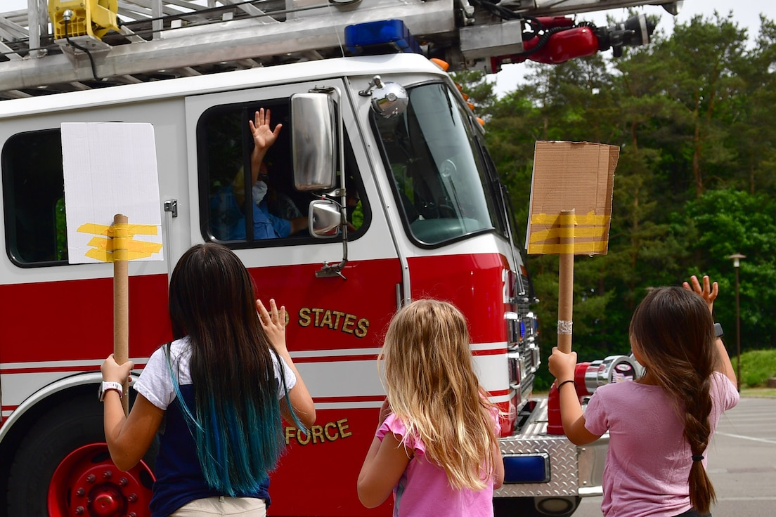 Three children hold signs and wave to first responders in a passing fire truck.