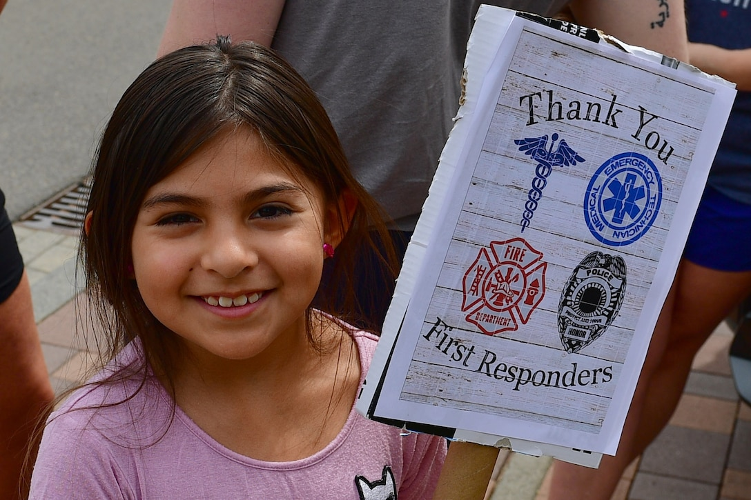 A child holds a thank you sign.