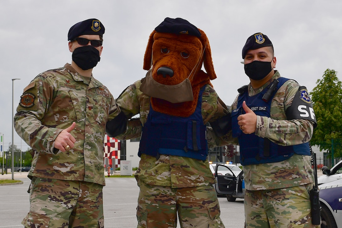 Two Airmen stand with McGruff the Crime Dog.