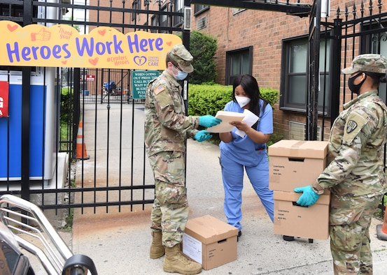 New York Army National Guard Pvt. Mathew Burke, left, from Mechanicville and Pfc. Janelle McKoy from New Windsor, both assigned to the 104th Military Police Battalion, deliver COVID-19 test kits to a nursing facility in The Bronx May 26, 2020.