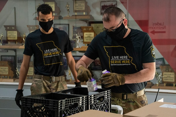 Spc. Ross Schlichting, left, and Staff Sgt. Vernon Long, with the 1221st Transport Company, Missouri National Guard, pack school lunches for delivery April 27, 2020, at Osage County R-II School, Linn, Missouri. Nearly 200 Guardsmen are assisting schools with distribution and delivery of food to students in communities across the state as part of the state's response to the COVID-19 pandemic.