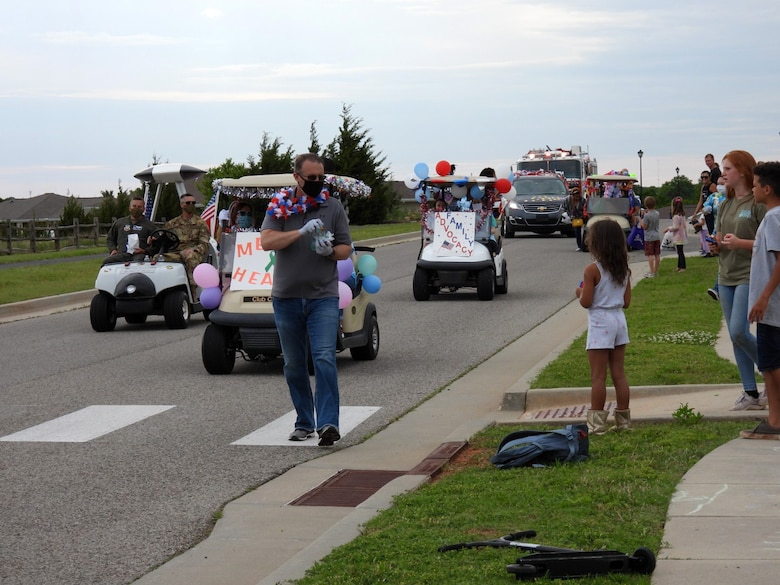 Members of Tinker's Helping Agencies handed out prepackaged bags of candy and goodie bags along the route of the Chalk It Up Parade May 27. Everyone participating in the parade wore masks and gloves.