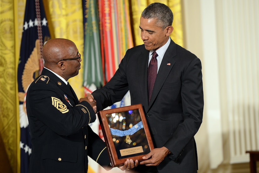 A man shakes hands with another man. Both hold a plaque.