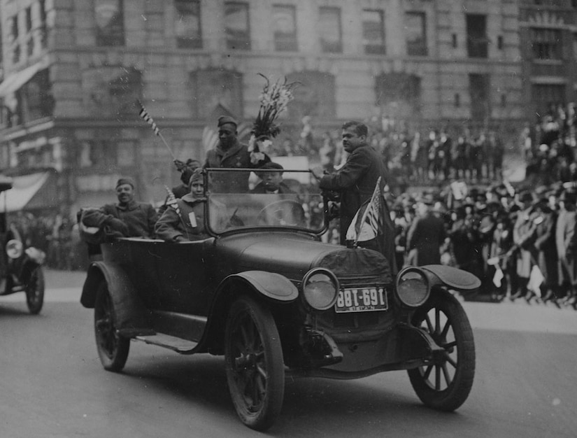 Two men stand and four others sit in a car as they wave to a crowd during a parade. One of the men who is standing is holding a bouquet of flowers.