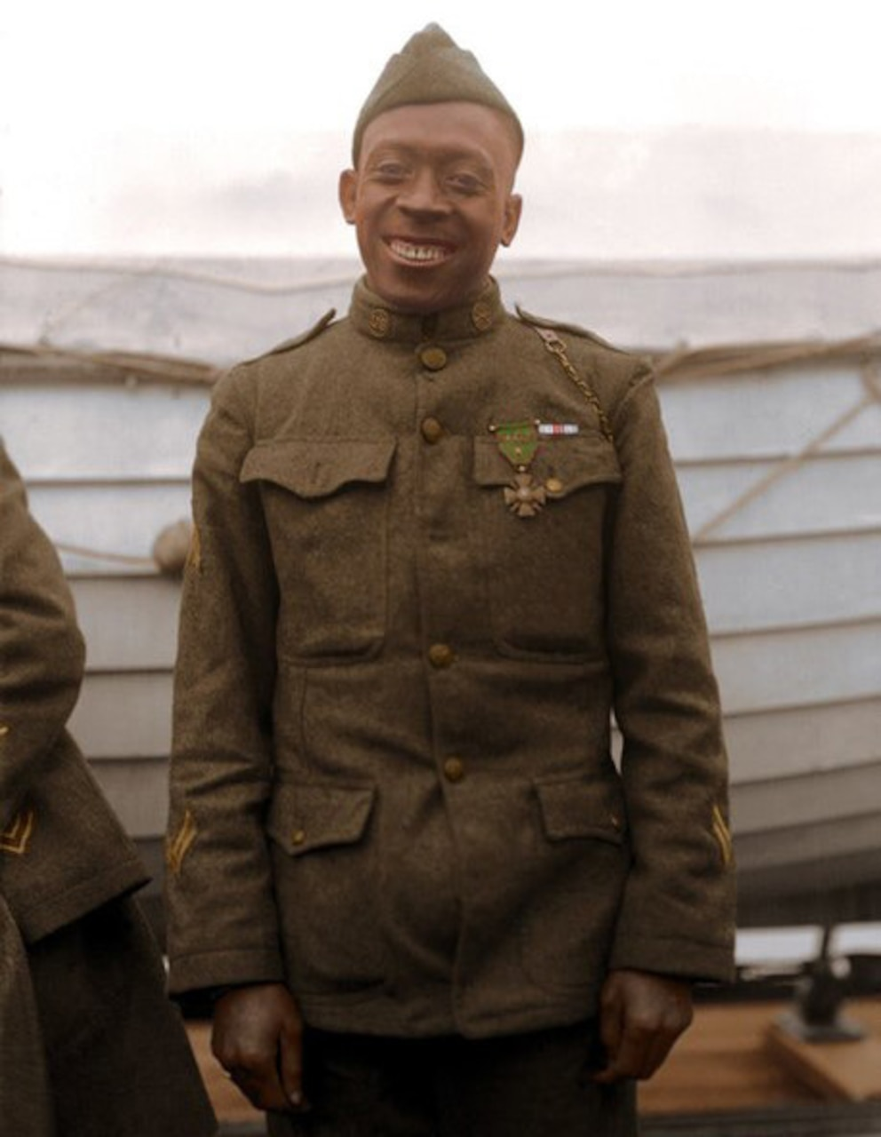 A man in a military uniform smiles for the camera.