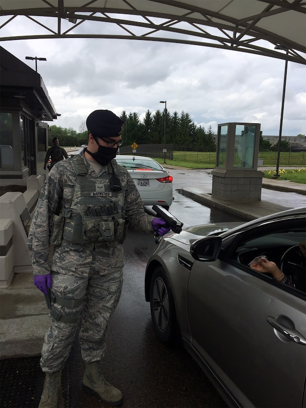 Senior Airman Aaron Marketich, 88th Security Forces Squadron, demonstrates the mask and gloves he and fellow defenders are utilizing during the COVID-19 situation on May 18 at Wright-Patterson Air Force Base's Gate 12A.