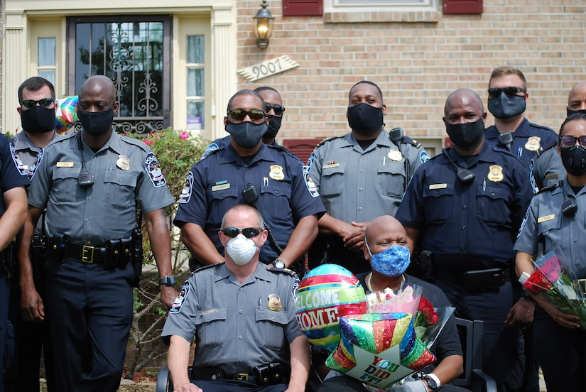 Police wearing protective face masks pose for a group photo.
