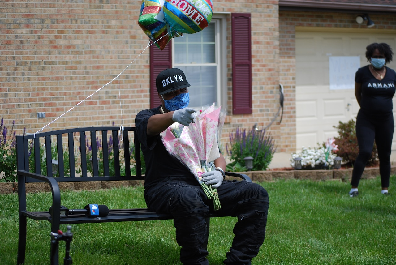 A man sits on a bench with flowers and balloons.