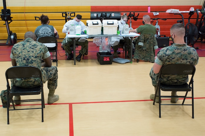Patrons wait to have their vitals checked during an Armed Services Blood Program (ASBP) blood drive at Hopkins Gymnasium on Camp Elmore, Norfolk, Virginia, May 28, 2020.