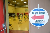 A welcoming signed is posted on the door of the Hopkins Gymnasium during an Armed Services Blood Program (ASBP) blood drive on Camp Elmore, Norfolk, Virginia, May 28, 2020.