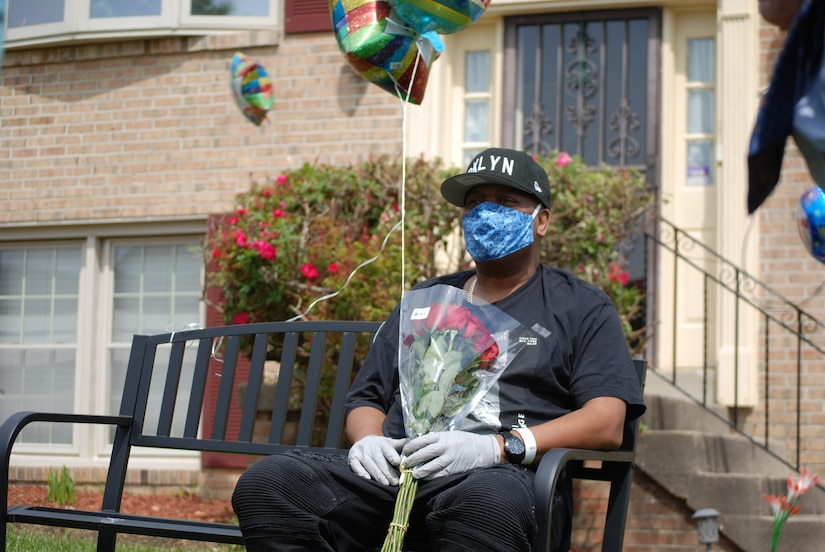 A man holding flowers and balloons sits on a bench.