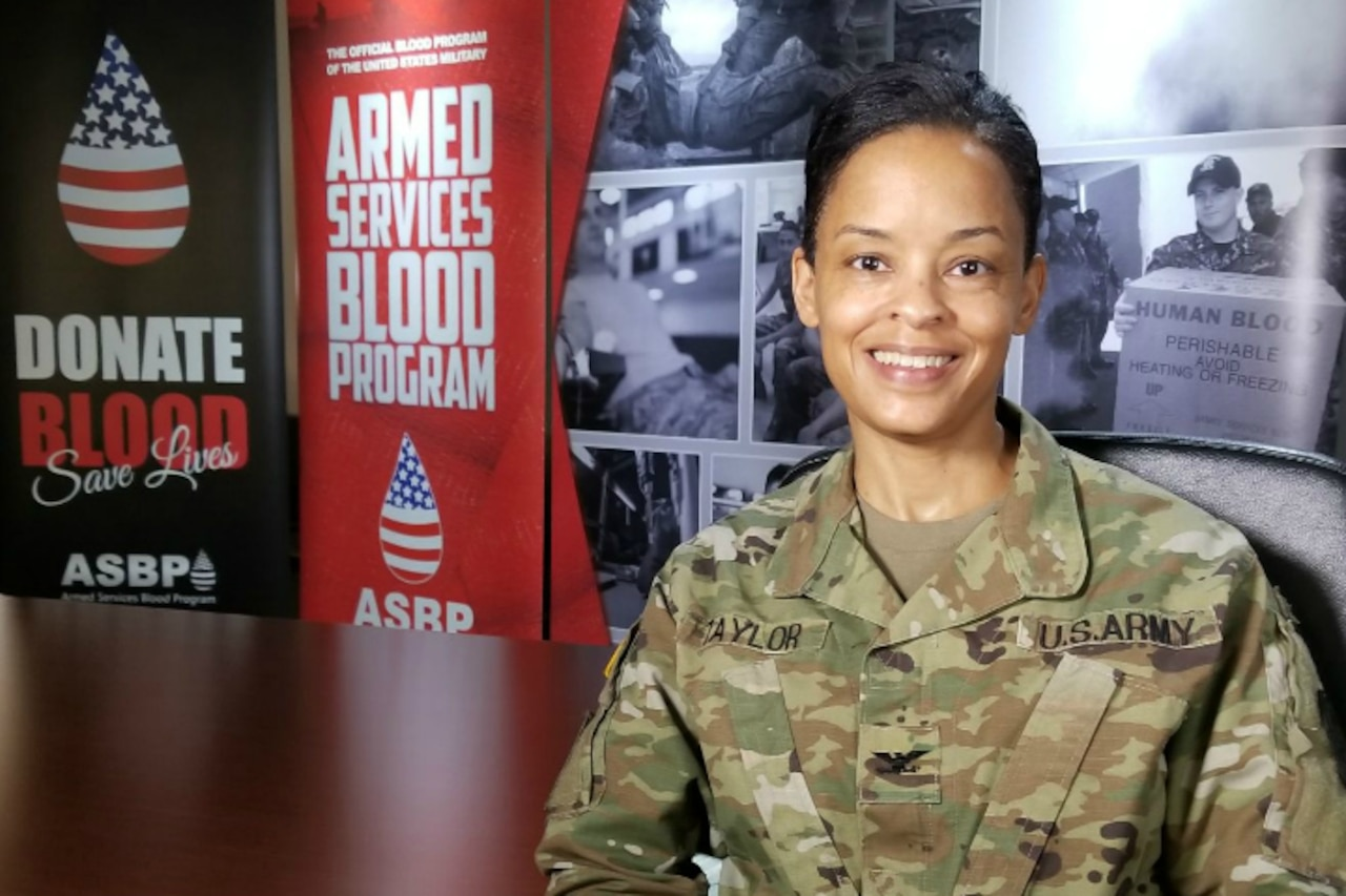 A woman in Army uniform sits in front of signs encouraging blood donation.