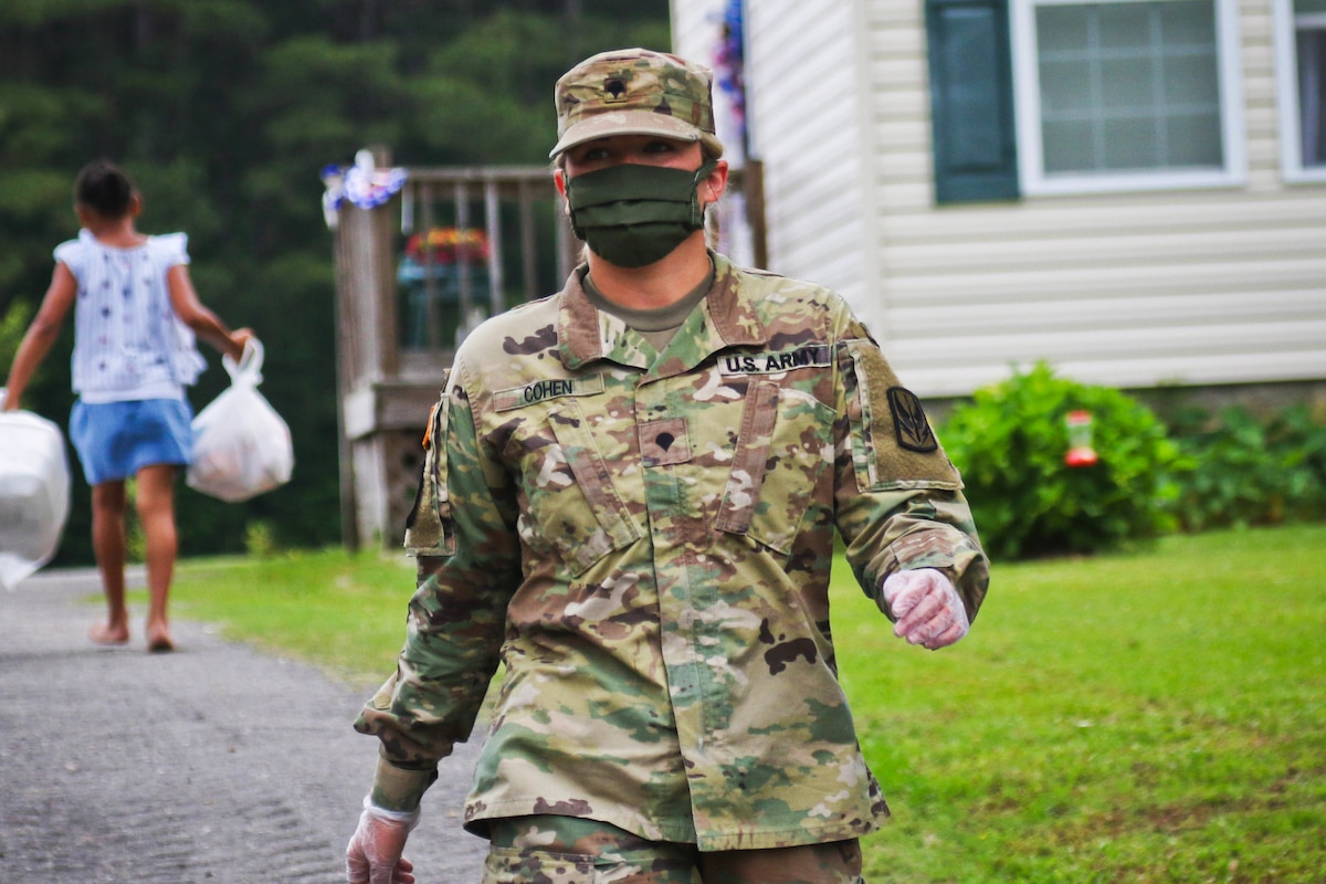 A soldier wearing a face mask walks down a driveway as a resident walks in the opposite direction carrying a bag in each hand.