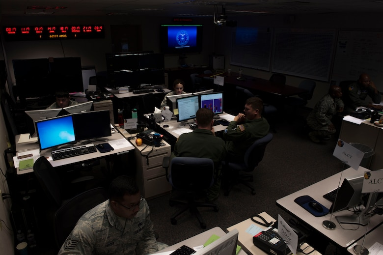 Members of the 621st Air Mobility Operations Squadron work during Exercise Mobility Guardian in the Weapon Systems Trainer at Joint Base McGuire-Dix-Lakehurst, N.J., August 1, 2017. The WST is designated as the primary air, space, and information operations command and control capability in support of any Joint Forces Commander or Joint Forces Air Component Commander. (U.S. Air Force photo by Tech. Sgt. Gustavo Gonzalez/RELEASED)