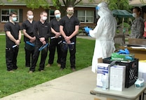 Col. Adam Colombo, senior medical adviser for Task Force-South, trains Task Force Iroquois personnel on proper personal protective equipment procedures at Hickory House Nursing Home in Honey Brook, Pa., on May 22, 2020.