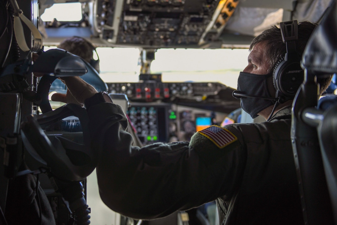 An airman touches buttons on an aircraft.