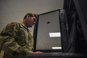 Senior Airman Alec Mellick, 22nd Communications Squadron server administrator, accesses a server to scan for vulnerabilities in the Air Force network May 8, 2020, at McConnell Air Force Base, Kansas. The 22nd CS continues to provide fast, mobile and reliable networks to more than 7,000 personnel assigned to McConnell AFB working at home through the fight against COVID-19. (U.S. Air Force photo by Airman 1st Class Marc A. Garcia)