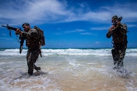 U.S. Marines with Lima Company, 3rd Battalion, 3d Marine Regiment, traverse through water during an amphibious assault exercise, Marine Corps Base Hawaii, May 28, 2020. Bravo Company, 1st Battalion, 3d Marine Regiment, and Lima Company, 3rd Battalion, 3d Marine Regiment, conducted an amphibious assault exercise and military operations in urban terrain to increase littoral mobility proficiency in 3d Marine Regiment and advance the goals of the Commandant of the Marine Corps 2030 Force Design. (U.S. Marine Corps photo by Cpl. Matthew Kirk)