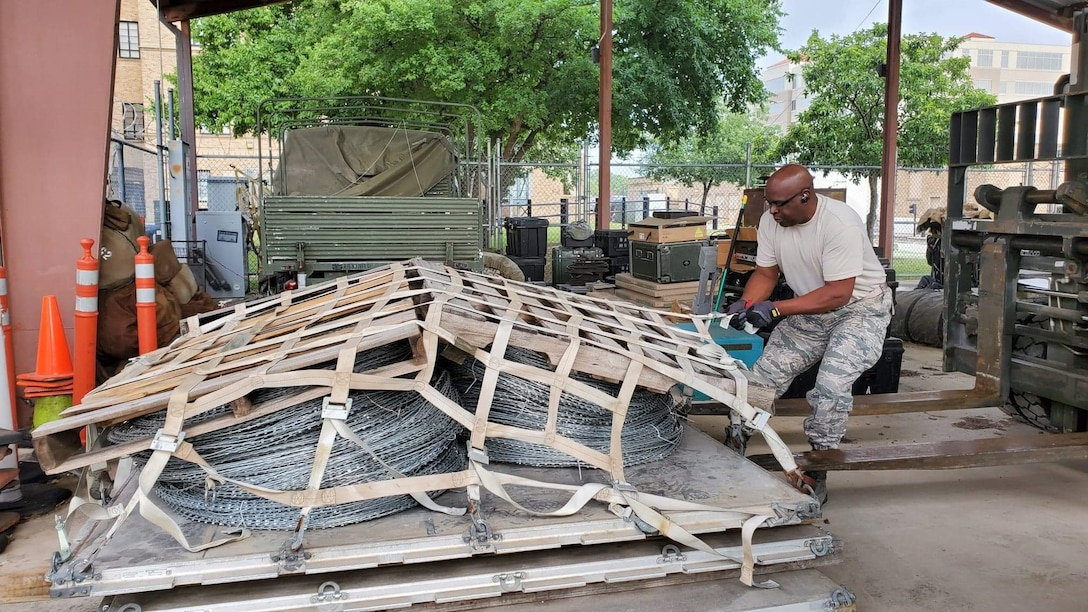 Tech. Sgt.  Ronald Hairston, a ground transportation operator with the 26th Aerial Port Squadron at Joint Base San Antonio-Lackland, Texas, secures concertina wire in preparation for shipping to the U.S. Army on May 22, 2020.