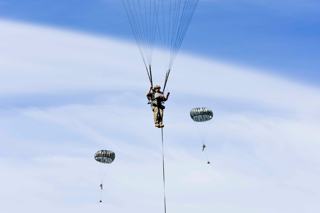 Three airmen descend in the sky wearing parachutes.